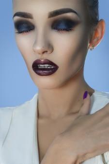 Sinnliche junge dame mit schönem make-up, geschlossenen augen und offenem mund im studio