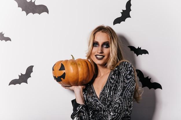 Sinnliche junge frau mit schwarzem make-up, das kürbis hält. spektakuläres mädchen, das sich auf halloween-party vorbereitet.