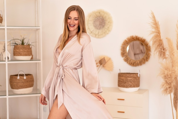Sinnliche junge hübsche blonde frau posiert im modernen trendigen boho-interieur mit luxuriösem seidenkimono