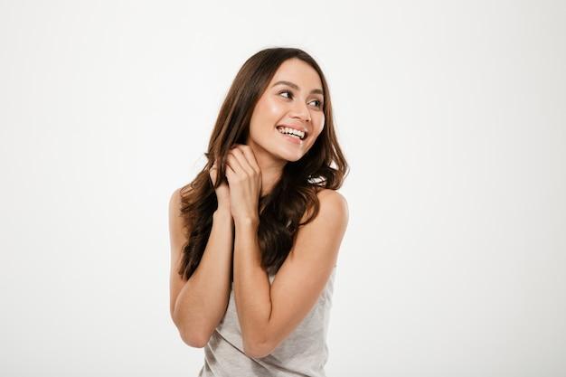 Sinnliche lächelnde brunettefrau, die weg über grau aufwirft und schaut