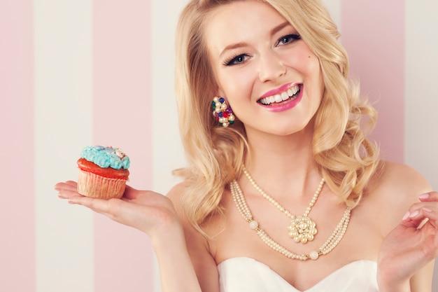 Sinnliche lächelnde frau, die mit blauem muffin aufwirft