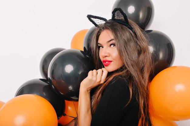 Sinnliche leicht gebräunte frau, die mit halloween-luftballons aufwirft