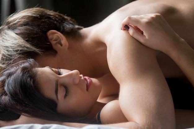 Sinnliche paare, die sex, den liebhaber der frau umfassen, der auf bett liegt