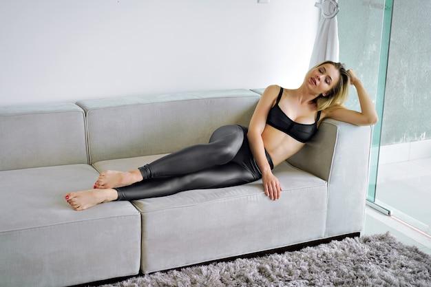 Sinnliche plünderungsfrau, die an stilvollen modernen schwarzen sportlichen kleidern am sofa aufwirft, passen perfekter körper, weiche natürliche farben.