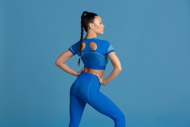 Sinnliche pose. schöne junge sportlerin üben, einfarbiges blaues porträt. sportlich fit brünettes model training. wellness, gesunder lebensstil, schönheit, bewegung und aktionskonzept.