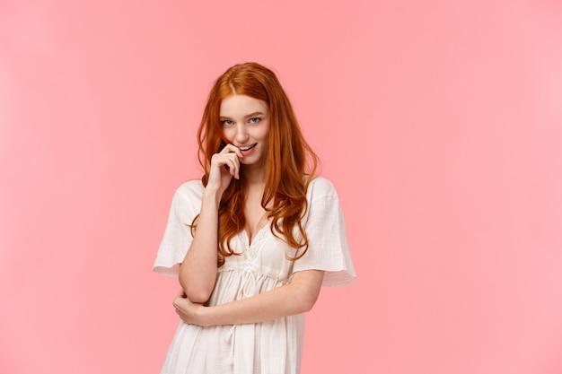 Sinnliche, romantische und freche, verführerische, rothaarige, verwegene frau in weißem kleid, beißender finger und koketter blick unter der stirn, rosa wand stehend, flirtend