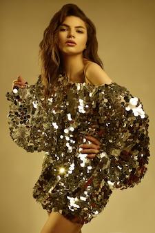 Sinnliche schöne brunettefrau in einem glänzenden modekleid von pailletten