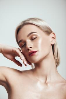 Sinnliche schönheit süße junge frau mit blonden haaren und perfekt glänzender haut, die die augen geschlossen hält