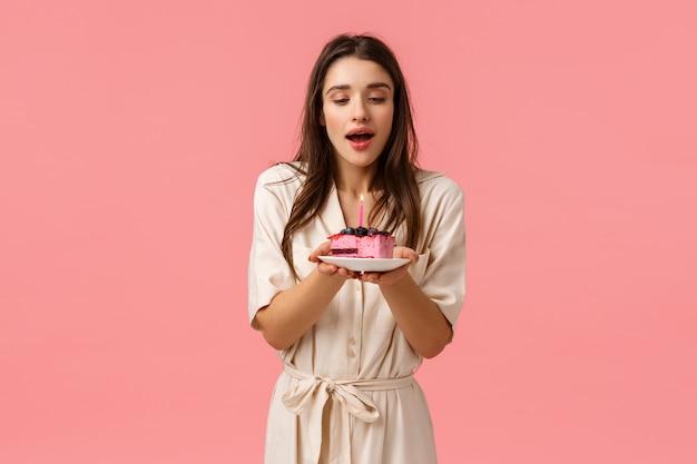 Sinnliche und zarte junge weibliche frau im kleid, teller mit köstlichem dessert, ausgeblasene geburtstagskerze halten und verträumt lächelnd, wunsch machen, alle wünsche zu erfüllen, stehende rosa wand
