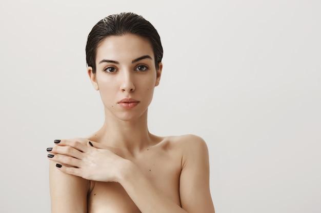 Sinnliche verträumte frau, die nackt steht und schulter berührt