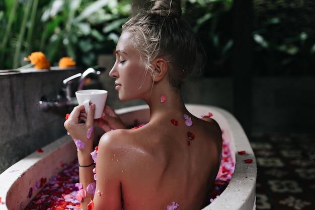 Sinnliche weiße frau mit blondem haar, das tee im bad trinkt. erstaunliche gebräunte dame, die spa mit geschlossenen augen tut und kaffee genießt.