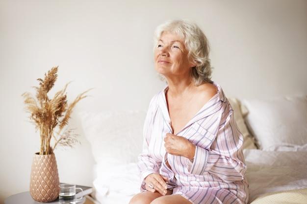 Sinnliche wunderschöne reife frau mit grauem haar genießt schönen sonnigen morgen im schlafzimmer, sitzt auf dem bett, zieht sich aus. pensionierte sexy kaukasische frau im schlafanzug, der zu hause entspannt