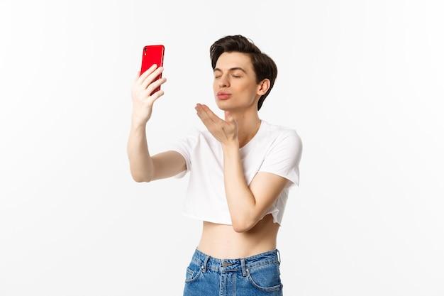 Sinnlicher schwuler mann in erntespitze, der selfie auf smartphone nimmt, luftkuss an telefonkamera sendet und augen träumerisch schließt, über weißem hintergrund stehend.