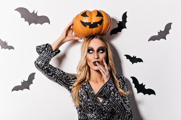 Sinnlicher weiblicher zauberer, der spielerisch in halloween aufwirft. innenaufnahme des schönen blonden vampirs.