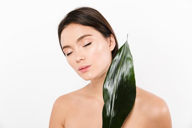 Sinnliches bild der weiblichen asiatischen frau 20s mit geschlossenen augen, die großes grünes blatt halten, lokalisiert über weiß