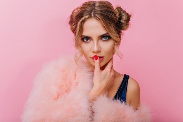 Sinnliches blauäugiges lockiges mädchen im flauschigen mantel, das im rosa raum steht und mit interesse schaut. entzückende junge frau mit dem trendigen make-up, das ihre lippen mit dem finger lokalisiert auf hellem hintergrund berührt