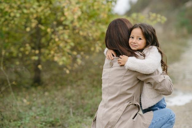Sinnliches foto. süßes kleines mädchen. die leute gehen nach draußen. frau in einem braunen mantel.