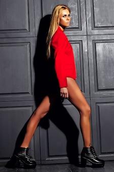 Sinnliches glamourmodeporträt des schönen bösen mädchens der schönen heißen blonden frau mit frischem täglichen make-up in der roten jacke, die nahe grauer wand geht