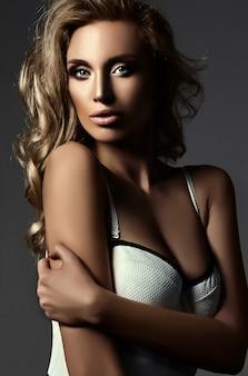 Sinnliches glamourporträt der schönen blonden frau model lady mit frischem make-up und gesundem lockigem haar