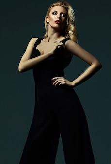 Sinnliches glamourporträt der schönen blonden frauenmodelldame mit frischem make-up im klassischen schwarzen kostüm