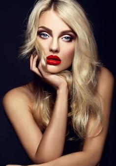 Sinnliches glamourporträt der schönen blonden frauenmodelldame mit hellem make-up und roten lippen, mit gesundem lockigem haar auf schwarzem hintergrund