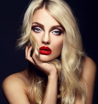 Sinnliches glamourporträt der schönen blonden modellfrau mit hellem make-up und roten lippen, die ihr gesicht berühren, mit gesundem lockigem haar auf schwarzem hintergrund