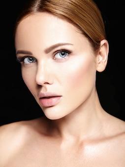 Sinnliches glamourporträt des schönen frauenmodells ohne make-up und saubere gesunde haut auf schwarz