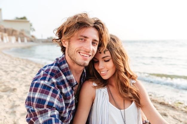 Sinnliches junges paar, das am strand sitzt und lächelt