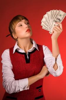 Sinnliches junges schönes mädchen in der freizeitkleidung hält eine packung dollar auf einem roten hintergrund