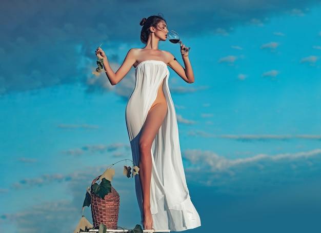 Sinnliches mädchen oder frau im weißen sexy kleid entblößt mit rotwein in glasgeflechtflaschenrebe und trauben auf natur über blauem himmel