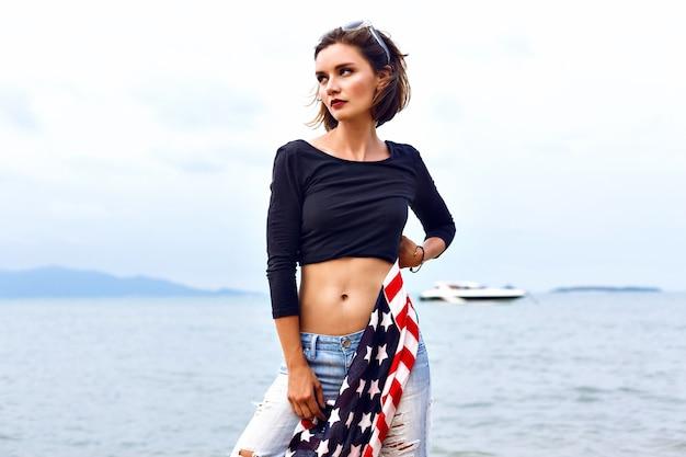 Sinnliches modeporträt der schönen traurigen frau, die am windigen regnerischen tag auf dem inselstrand aufwirft, outfit der alten schule tragend, sexy bode passen, amerikanische flagge in ihren händen halten.