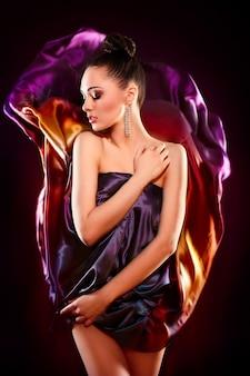 Sinnliches modeporträt des schönen sexy brünetten mädchenmodells, das im hellen bunten fliegenden kleid aufwirft, birght make-up lokalisiert im schwarzen hintergrund