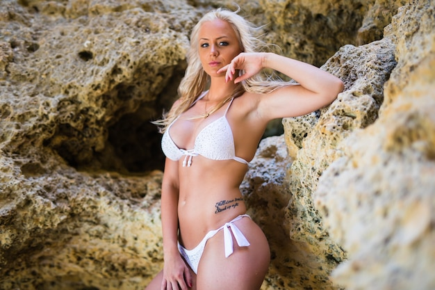 Sinnliches nasses bikinimodell in den meereswellen. sorglose frau, die schönen sonnenuntergang am felsenstrand genießt
