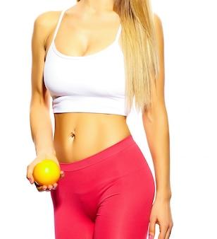 Sinnliches porträt des jungen sportfrauenmädchens des schönen sports mit perfektem körper mit orange