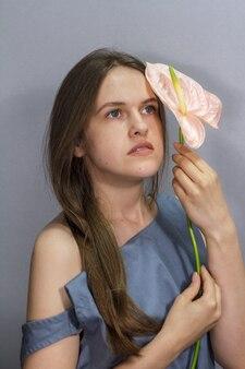 Sinnliches porträt des langhaarigen brünetten mädchens mit rosa anthuriumblume auf grauem hintergrund