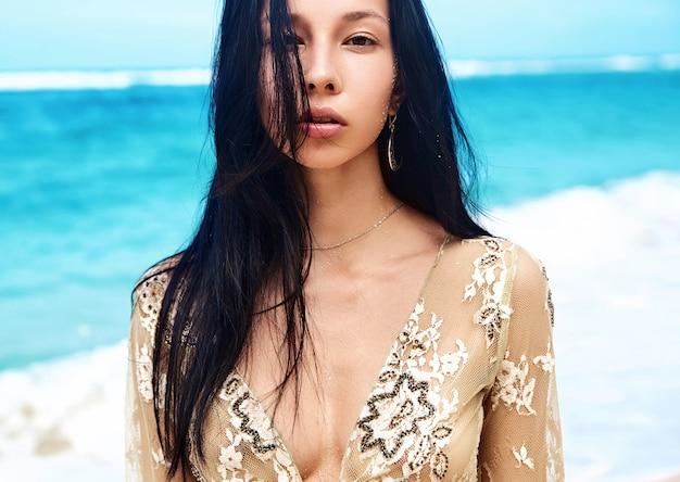 Sinnliches porträt des schönen kaukasischen frauenmodells mit dunklem langem haar in der beigen bluse, die auf sommerstrand mit weißem sand auf blauem himmel und ozeanhintergrund aufwirft