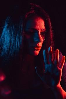 Sinnliches porträt des traurigen mädchens durch glas mit regentropfen mit roter blauer beleuchtung