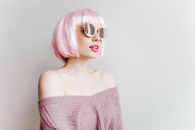 Sinnliches reizendes mädchen in der rosa perücke, die auf lichtwand aufwirft. innenporträt der hübschen frau in gestrickter lila kleidung stehend