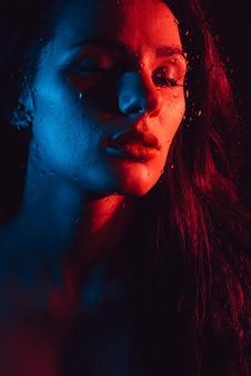 Sinnliches schönheitsmodeporträt des sexy brunettemädchens durch glas mit regentropfen