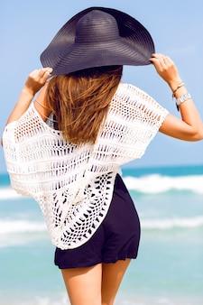 Sinnliches sommermodeporträt der eleganten dame, die hut und boho-schickes outfit trägt, das an erstaunlichem tropischem strand mit blauem klarem meer aufwirft. bleib zurück und schau zum meer und genieße ihren urlaub