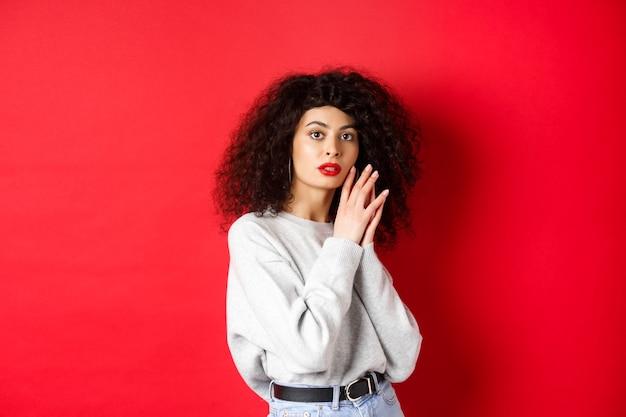 Sinnliches und romantisches mädchen mit lockigem haar und roten lippen, das gesicht sanft mit make-up berührt und vor rotem hintergrund steht.