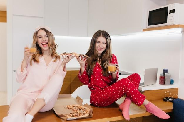 Sinnliches weißes mädchen, das pizza hält und in der küche aufwirft. innenfoto von zwei hübschen schwestern, die morgen zusammen verbringen und saft trinken.