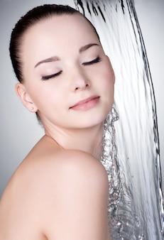 Sinnlichkeitsfrau mit geschlossenem auge unter dem strom des sauberen wassers - grauer hintergrund