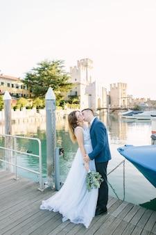Sirmione, gardasee, italien. charmantes verliebtes paar, das sich auf der brücke in sirmione umarmt und küsst