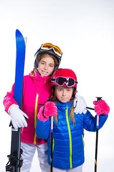 Siters kinder mädchen mit skistöcken helm und schneebrille