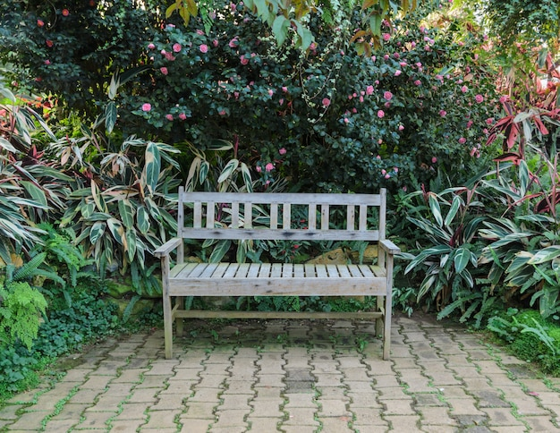 Sitzbank im grünen garten mit blumenpflanze