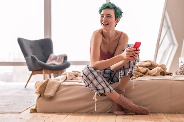 Sitzen auf dem bett. grünhaarige frau, die auf dem bett sitzt und rotes smartphone benutzt, während sie online-nachrichten liest reading