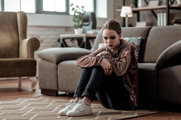 Sitzen auf dem boden. teenager-mädchen mit weißen turnschuhen, die auf dem boden in der nähe des sofas sitzen und sich gestresst fühlen