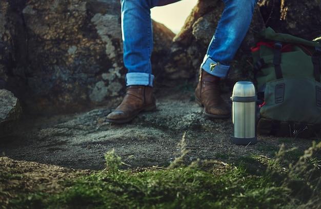 Sitzen auf einem rockmann in blue jeans und alten braunen schuhen. metallthermosflasche, rucksack im vordergrund. nahaufnahme der nicht erkennbaren person