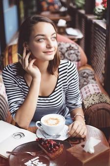 Sitzen der jungen frau innen im städtischen café